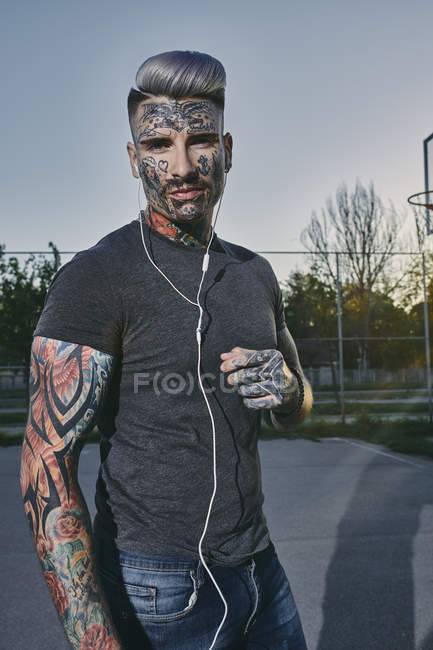 Portrait of tattooed young man listening to music with earbuds — Stock Photo