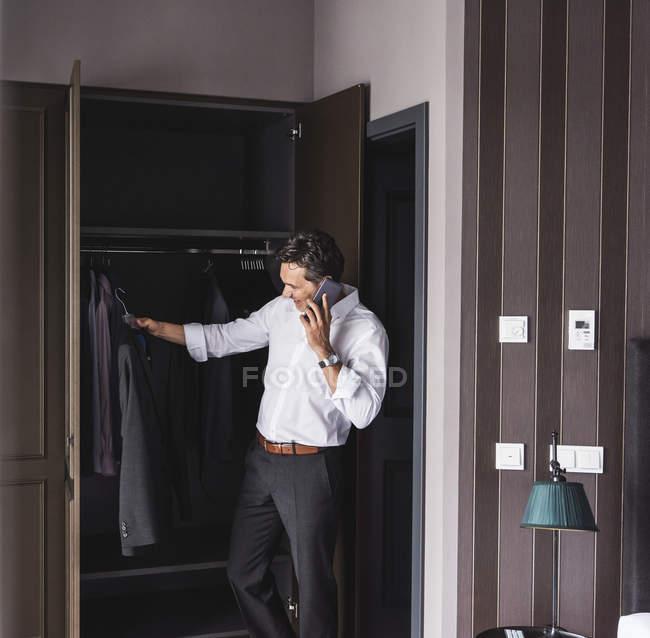 Empresário sorridente no celular em casa se vestindo — Fotografia de Stock