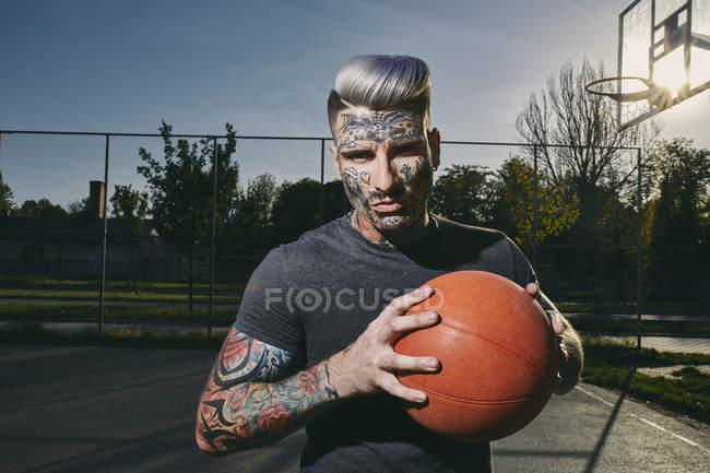 Портрет татуированного молодого человека с баскетболом на площадке — стоковое фото