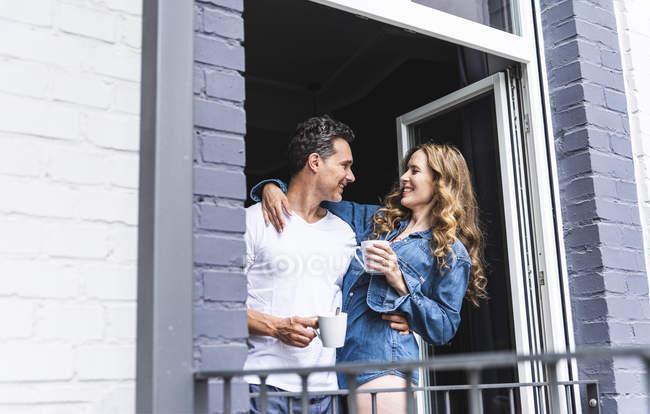 Pareja sonriente en ropa de dormir en casa con tazas de café en la puerta del balcón - foto de stock