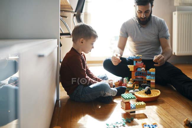 Vater spielt zu Hause mit Ziegelsteinen auf dem Boden und ignoriert seinen traurigen kleinen Sohn, der neben ihm sitzt — Stockfoto