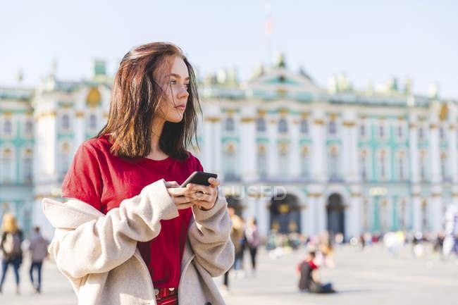 Rusia, San Petersburgo, mujer joven usando smartphone en la ciudad - foto de stock