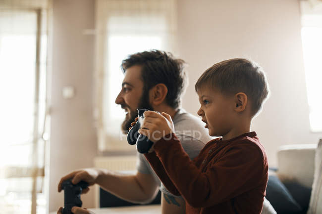 Little boy playing computer game with his father at home — Stock Photo