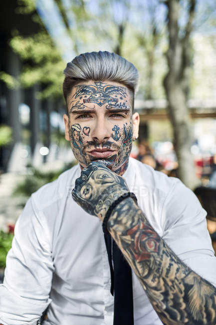Young businessman with tattooed face, looking at camera — Stock Photo