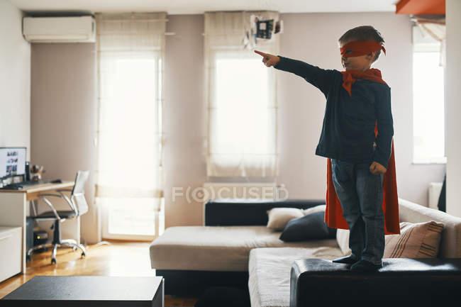 Petit garçon rectifié vers le haut comme un super-héros restant sur la table basse à la maison pointant sur quelque chose — Photo de stock