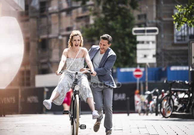 Heureux couple insouciant avec vélo dans la ville — Photo de stock