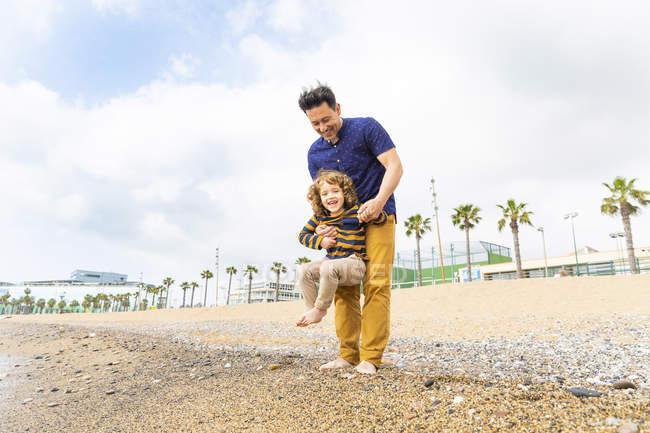 Испания, Барселона, отец держит сына на пляже — стоковое фото
