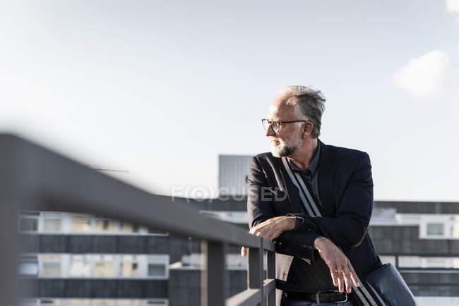 Reifer Mann steht auf Dach und lehnt sich an Geländer — Stockfoto