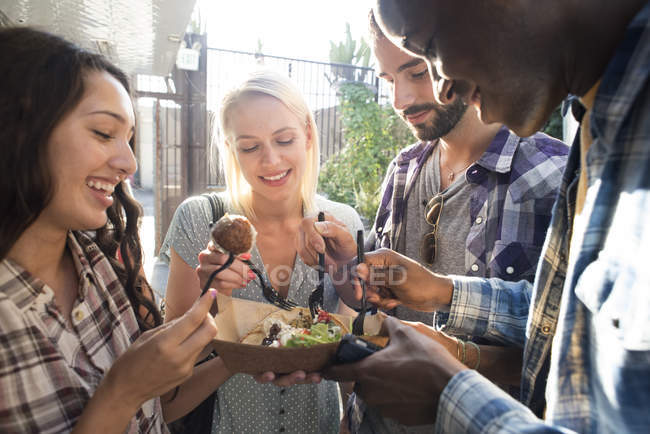 Amigos felizes que compartilham do alimento takeaway ao ar livre — Fotografia de Stock