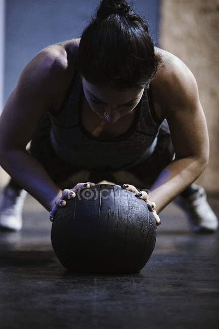 Woman doing push ups on ball in gym — Stock Photo