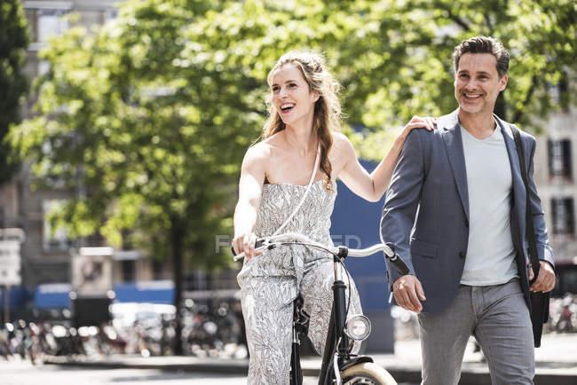 Счастливая пара с велосипедом в городе — стоковое фото