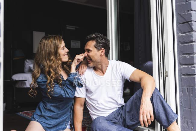 Грайливий пара в нічний одяг вдома сидячи на французькому вікні — стокове фото