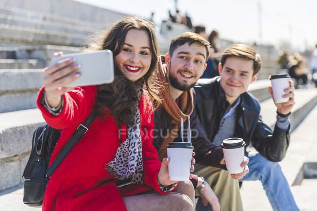 Россия, Москва, группа друзей, делающих селфи и показывающих чашки кофе — стоковое фото