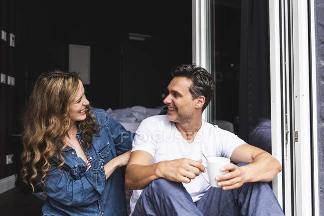 Happy couple in nightwear at home sitting at French window — Stock Photo