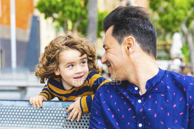 Padre e hijo jugando y mirándose - foto de stock