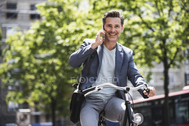 Smiling man on cell phone riding bike in the city — Stock Photo