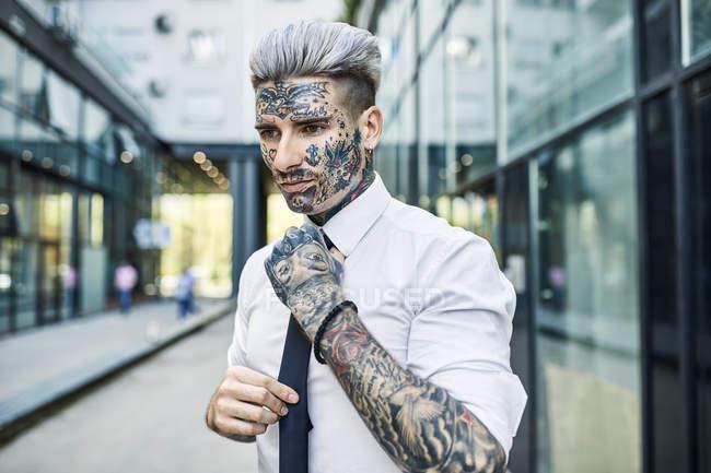 Молодой бизнесмен с татуированным лицом, застегивающий галстук — стоковое фото