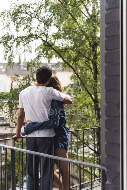 Rear view of couple in nightwear standing on balcony hugging — Stock Photo