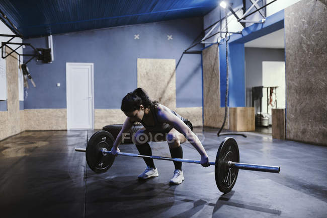 Woman preparing for weightlifting in gym — Stock Photo
