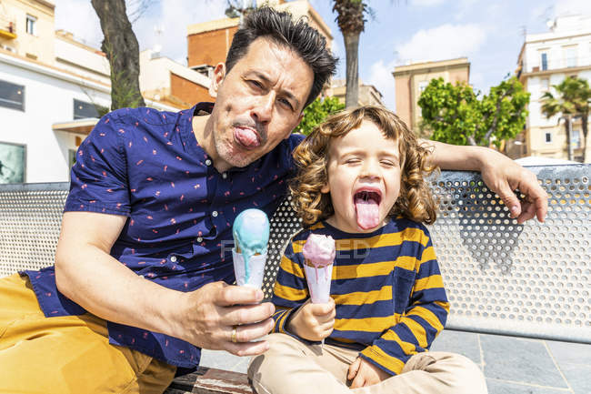 Spain, Barcelona, happy father and son sitting on bench enjoying an ice cream — Stock Photo