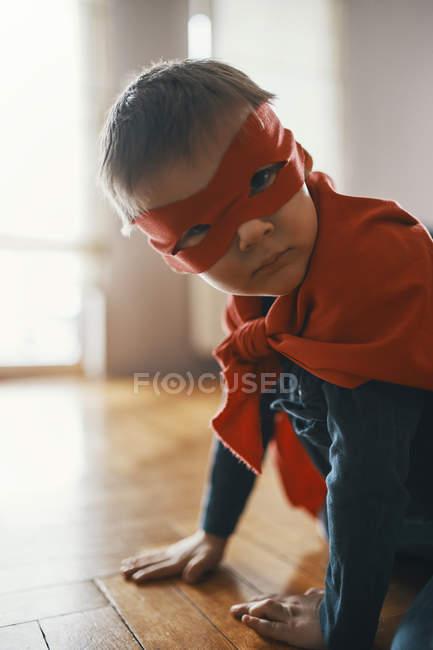 Petit garçon rectifié vers le haut en tant que super-héros accroupi sur l'étage à la maison — Photo de stock