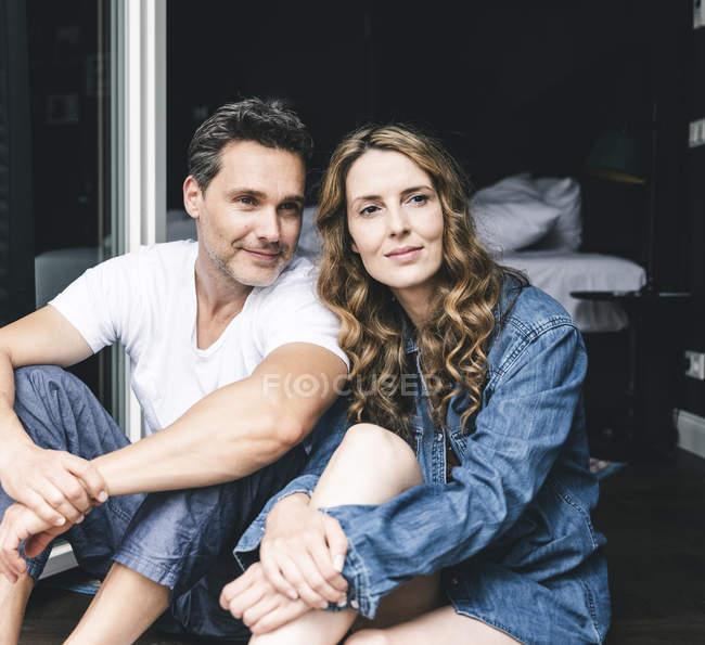 Усміхнена пара в нічний одяг вдома, сидячи на французькому вікні — стокове фото
