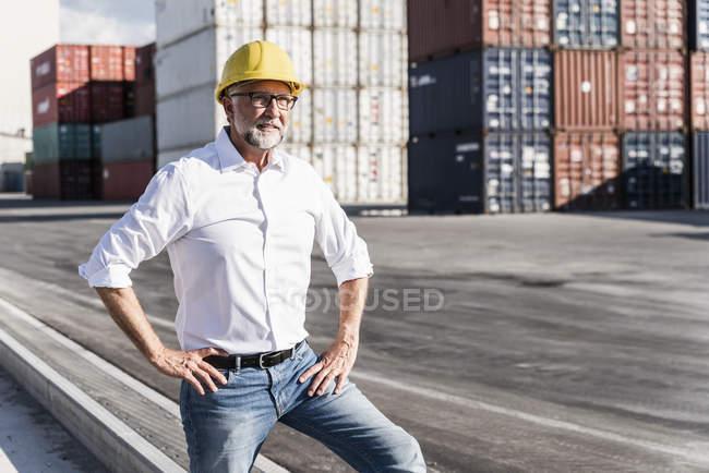 Businessman at cargo harbour, wearing safety helmet, portrait — Stock Photo
