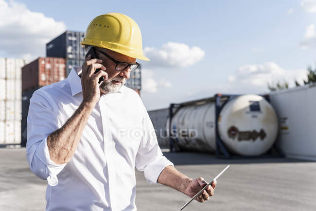 Businessman at cargo harbour, wearing safety helmet, using smartphone and digital tablet — Stock Photo