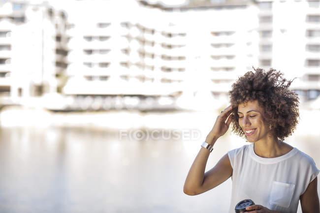 Mujer joven tomando un descanso al aire libre, sosteniendo una taza de café - foto de stock
