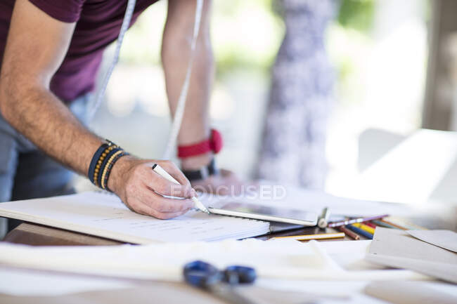 Close-up of fashion designer taking notes on table — Stock Photo