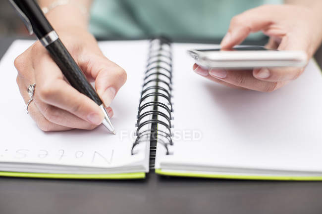Жінка пише нотатки в щоденнику, тримаючи смартфон. — стокове фото