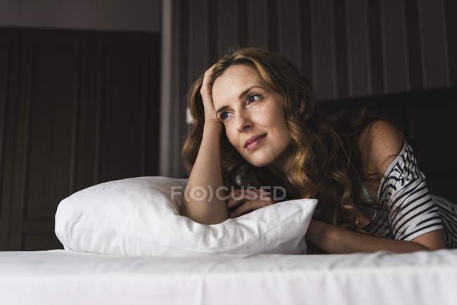 Задумчивая женщина лежит дома и смотрит в сторону. — стоковое фото