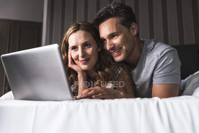 Sorridente coppia sdraiata sul letto a casa guardando il computer portatile — Foto stock