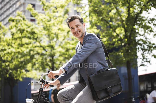 Uomo sorridente in bicicletta in città — Foto stock