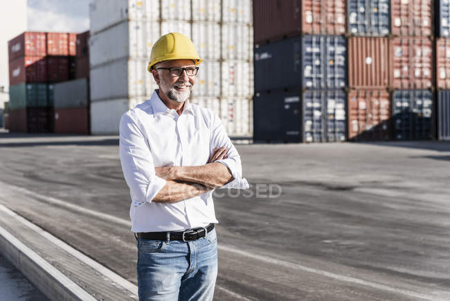 Businessman at cargo harbour, wearing safety helmet, arms crossed — Stock Photo