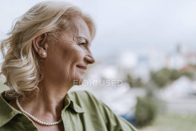 Smiling senior woman with hearing aid outdoors — Stock Photo