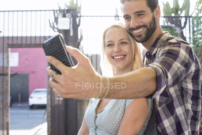 Happy young man with girlfriend taking a selfie — Stock Photo