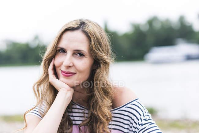 Portrait de femme souriante au bord de la rivière — Photo de stock