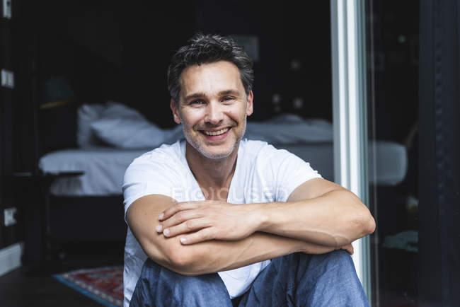 Retrato de homem sorridente em pijama em casa sentado na janela francesa — Fotografia de Stock