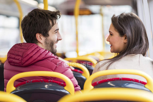 UK, London, happy young couple sitting side by side in bus — Stock Photo