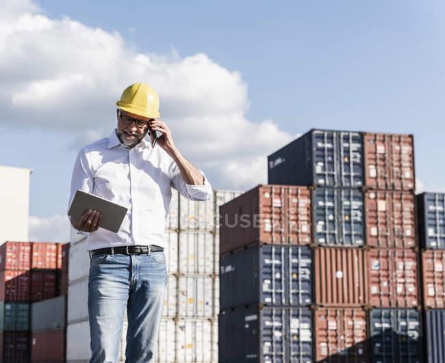 Businessman at cargo harbour, weraing safety helmet, using smartphone and digital tablet — Stock Photo