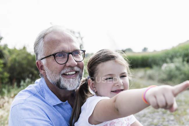 Feliz pai e filha se divertindo, menina apontando — Fotografia de Stock