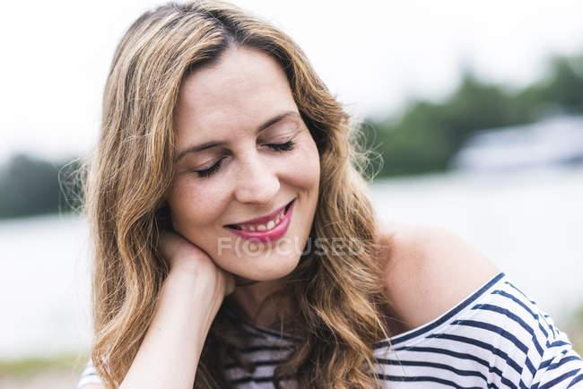 Retrato de mulher sorridente à beira do rio — Fotografia de Stock