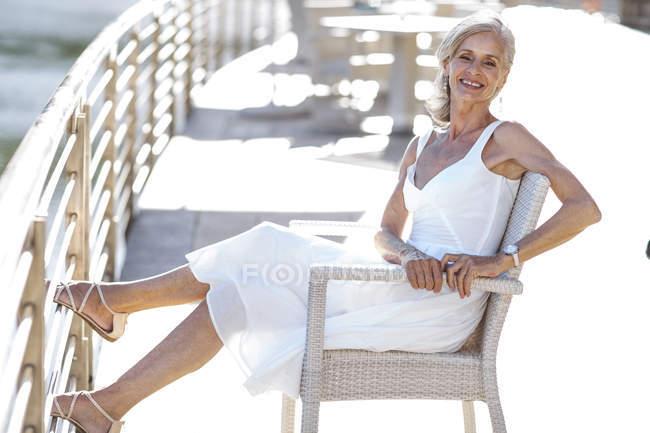 Старшая женщина расслабляется на скамейке — стоковое фото