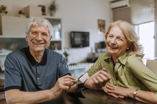 Lächelndes Seniorenpaar mit Blutdruckmessgerät — Stockfoto