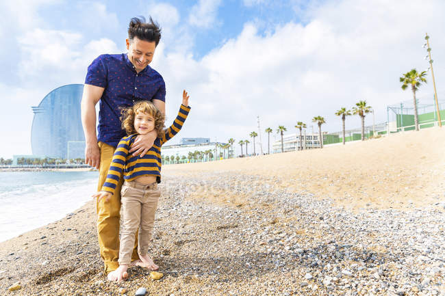 Spain, Barcelona, young boy with feet over his father on beach with pebbles — Stock Photo
