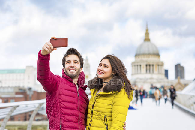 UK, London, portrait of smiling young couple taking selfie with cell phone in front of St Pauls Cathedral — Stock Photo