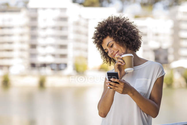 Young woman taking a break outdoors, holding cup of coffee and smartphone — Stock Photo