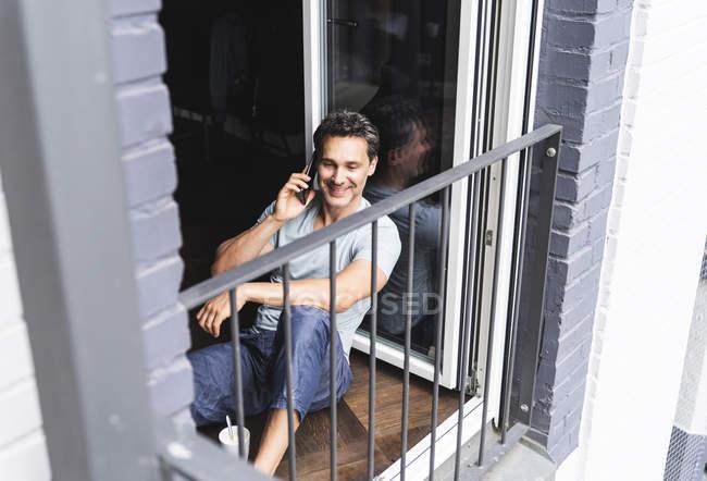 Улыбающийся мужчина в пижаме дома по мобильному телефону у двери балкона — стоковое фото