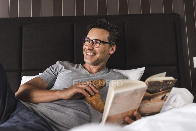Happy man lying in bed at home with croissant and book — Stock Photo